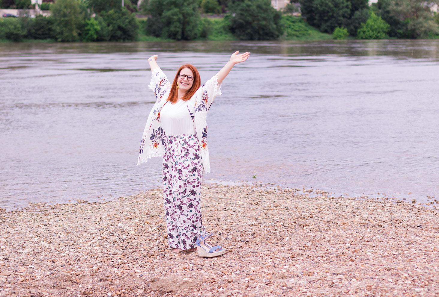 Les bras en l'air et les chaussures compensées Cendriyon posées aux pieds sur le sable, sur les bords de la Loire