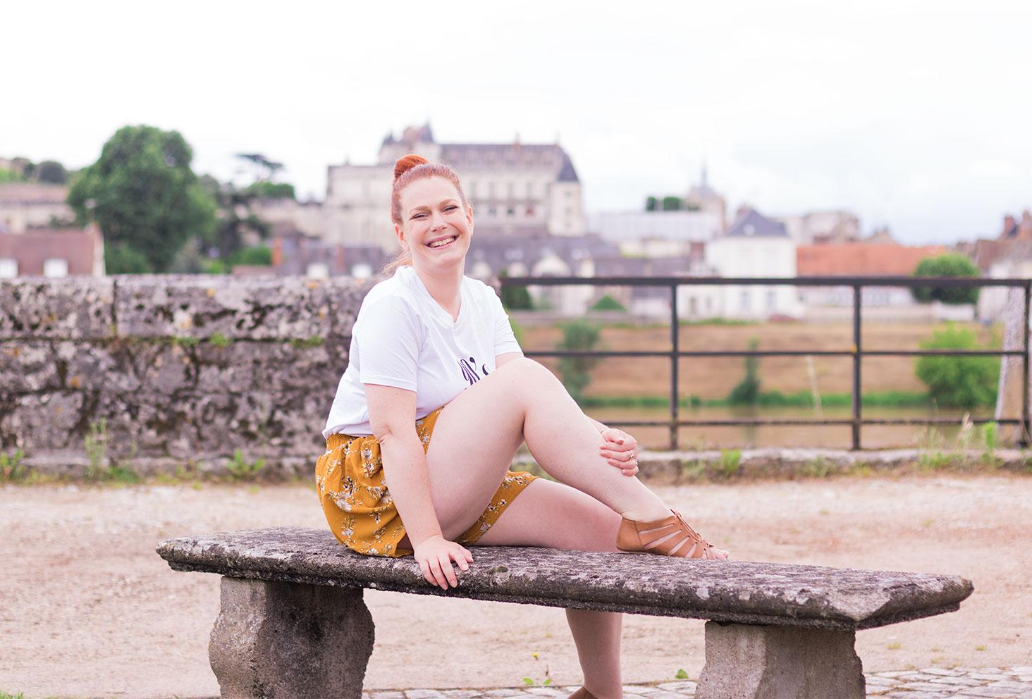Assise de profil sur un banc avec le château d'Amboise en arrière plan, en look Shein, avec le sourire et un chignon sur la tête