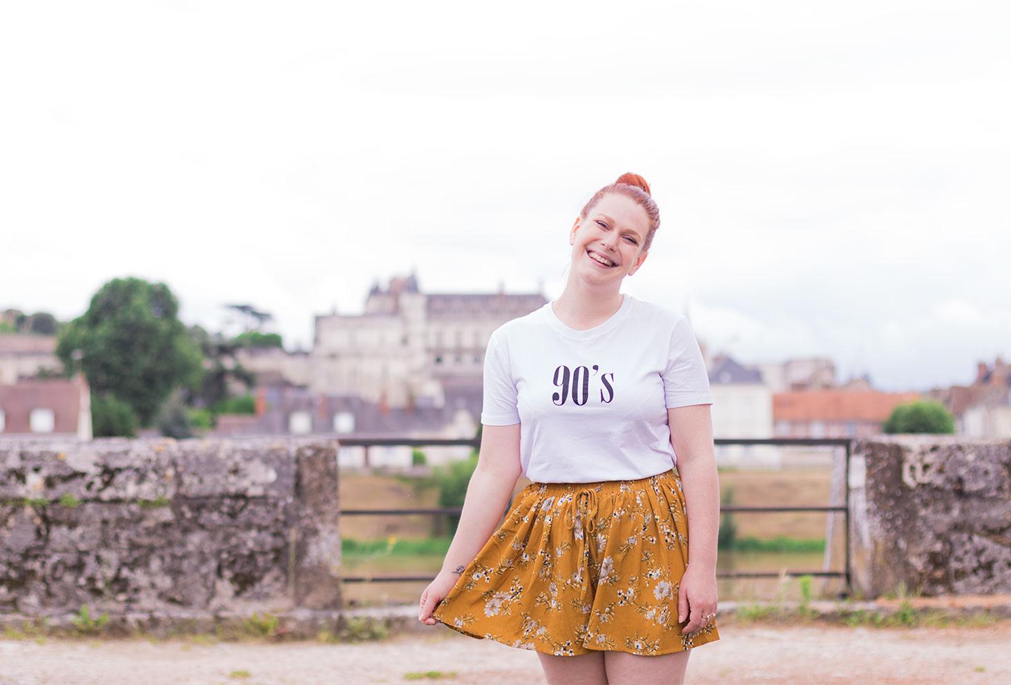 Devant le château d'Amboise en jupe short jaune moutarde à fleurs et t-shirt blanc 90's SheIn, avec le sourire