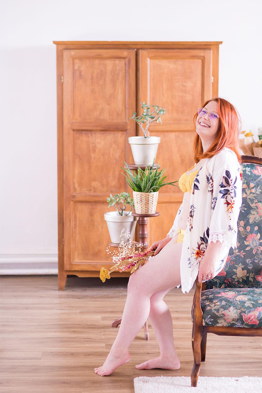 Assise de profil sur l'accoudoir d'un fauteuil ancien, en kimono et sous-vêtements, au milieu d'un salon