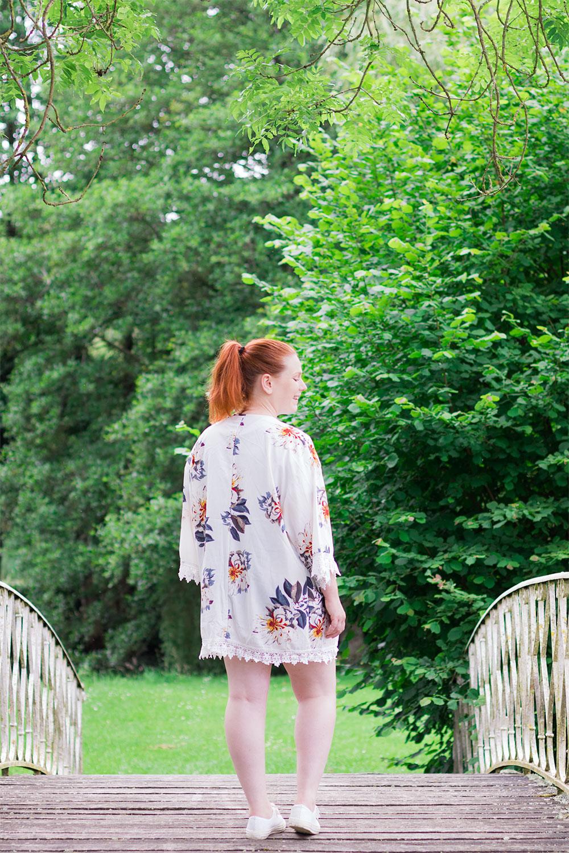 De dos sur une passerelle en bois et fer forgé avec un kimono à fleurs SheIn