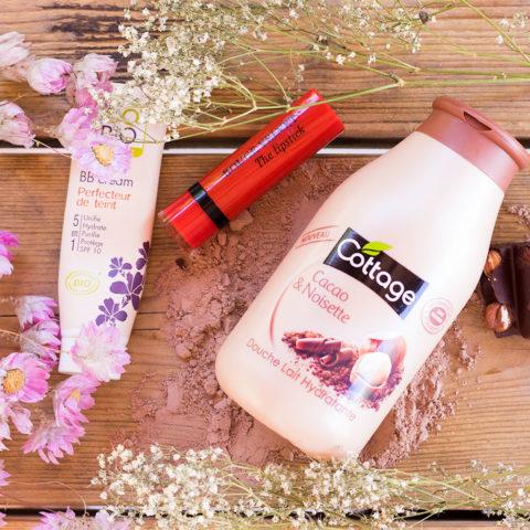 La BB crème de SO'Bio étic, le gel douche cacao noisette de Cottage et le Velvet The Lipstik rouge de Bourjois sur une table en bois au milieu des fleurs séchées et des carreaux de chocolat