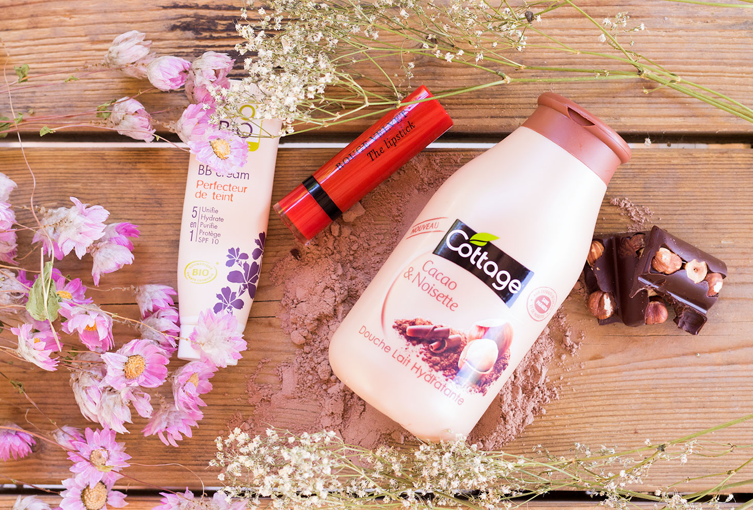 La BB crème de SO'Bio étic, le gel douche cacao noisette de Cottage et le Velvet The Lipstik rouge de Bourjois sur une table en bois au milieu des fleurs séchées et des carreaux de chocolat