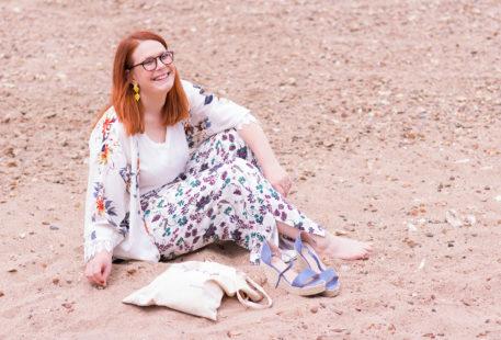 Assise dans le sable de la plage des bords de Loire. En pantalon fluide à fleurs et kimono, les chaussures compensées Cendriyon posées à côté des pieds et d'un tote bag en lin