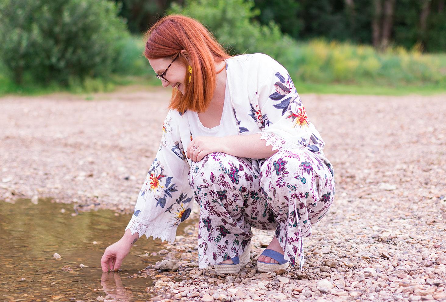 Accroupie sur le sable une main dans l'eau, avec le sourire, en kimono et pantalon à fleurs, les compensées Cendriyon aux pieds