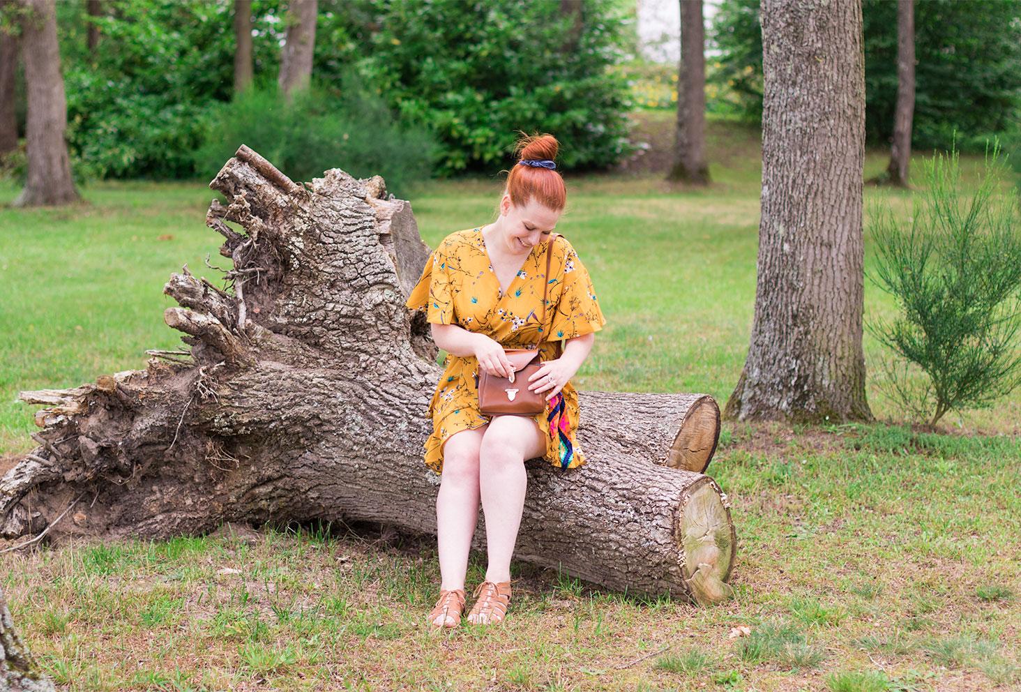 Assise sur une cime d'arbres au milieu de la forêt en robe portefeuill jaune moutarde SheIn et sac marron