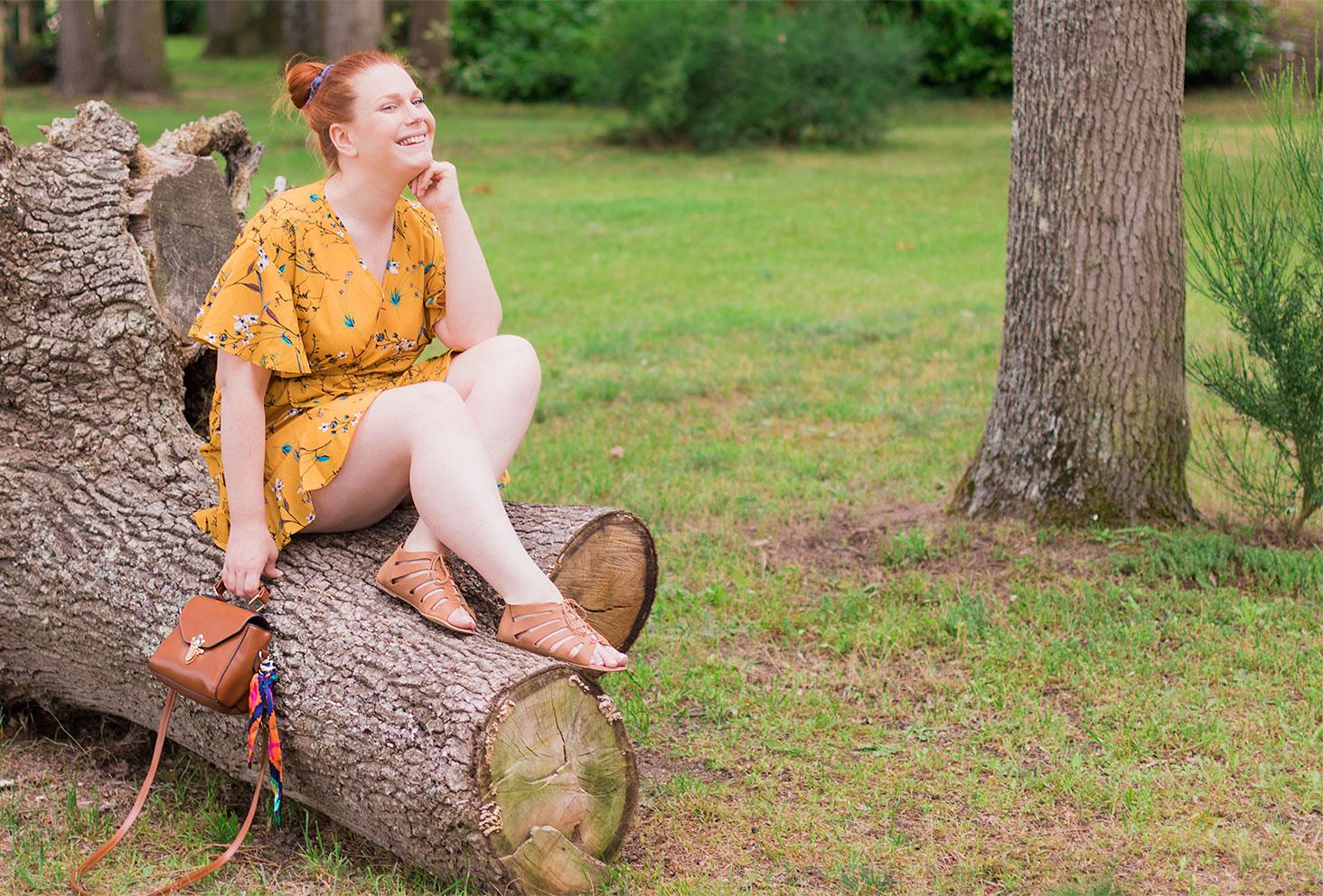 En robe portefeuille sur une cime d'arbre au milieu de la forêt, un petit sac marron SheIn dans la main, avec le sourire