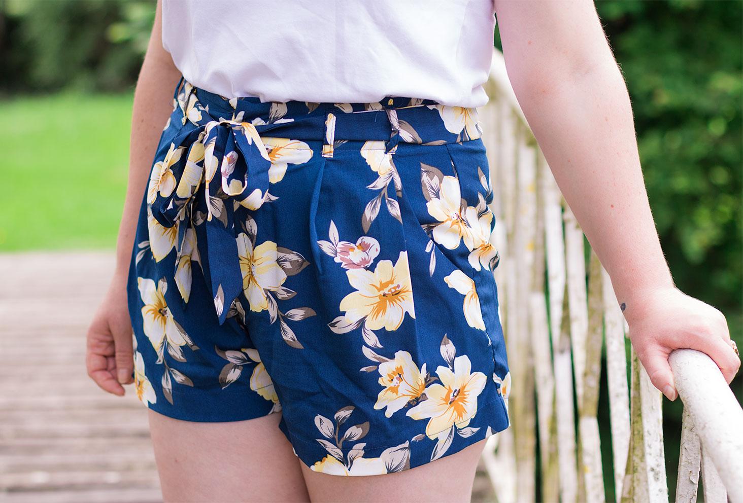 Zoom sur un short à fleurs fluide bleu marine porté