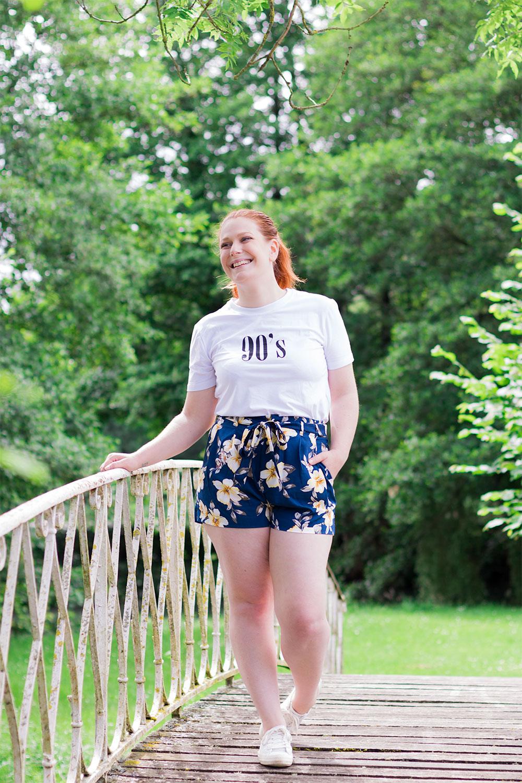 Sur un vieux pont en bois et fer forgé en t-shirt 90's et short à fleurs SheIn