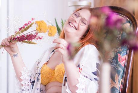 Zoom sur le kimono fleuri et le soutien-gorge en dentelle jaune moutarde, le sourire jusqu'aux oreilles, assise sur un fauteuil vintage en bois