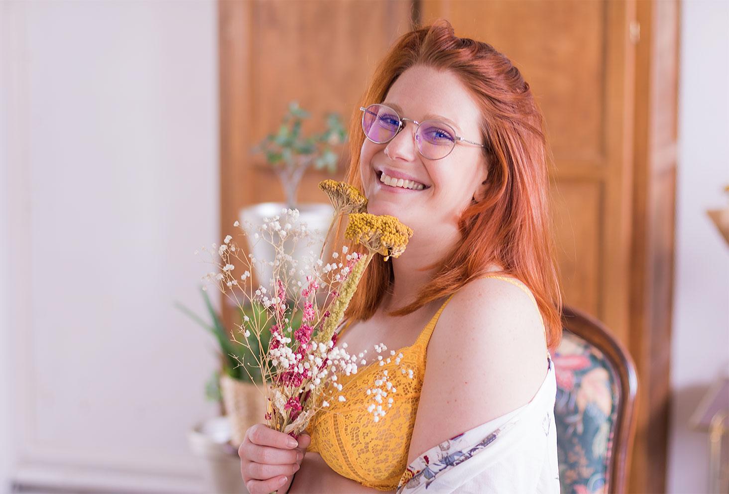 Zoom sur le soutien-gorge jaune en dentelle Pomm'Poire, de profil avec un bouquet de fleurs sèches entre les mains avec le sourire