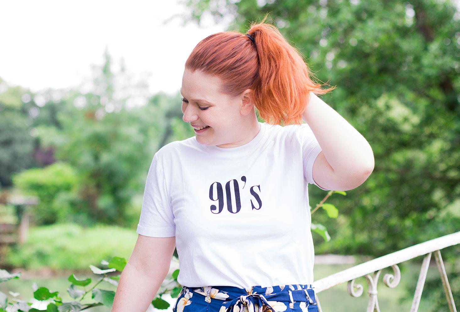De face, t-shirt SheIn 90's porté, contre une rambarde en fer forgé blanche au milieu de la verdure