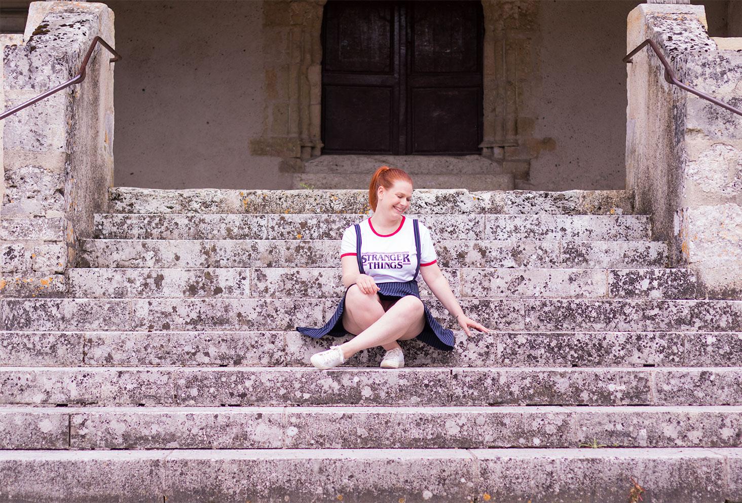 Assise au milieu des marches d'une ancienne cathédrale en jupe à bretelle et t-shirt Stanger Things SheIn