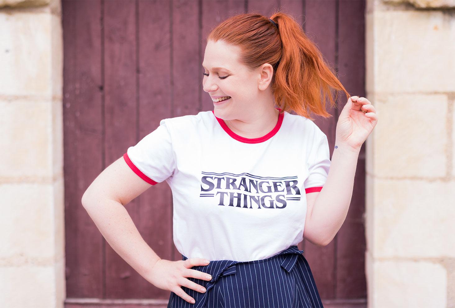 Pose devant une vieille porte en bois avec le sourire et un t-shirt blanc et rouge Stanger Things de SheIn