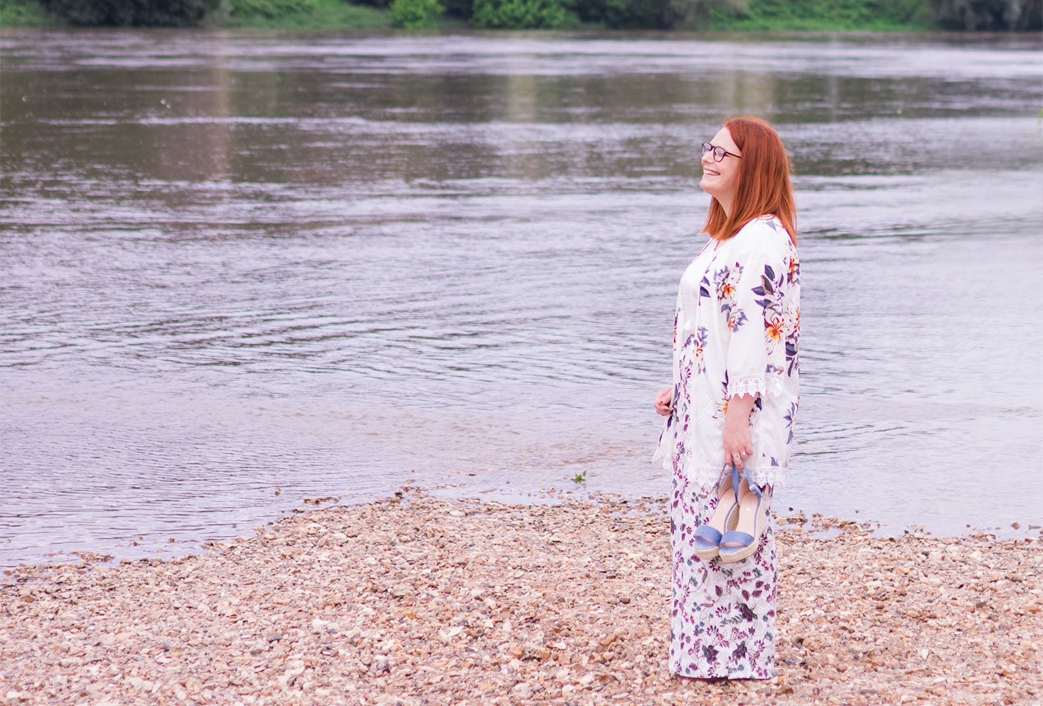 Sur la plage dans le sable des bords de Loire, en kimono et pantalon à fleurs, de profil les chaussures compensées Cendriyon dans la main