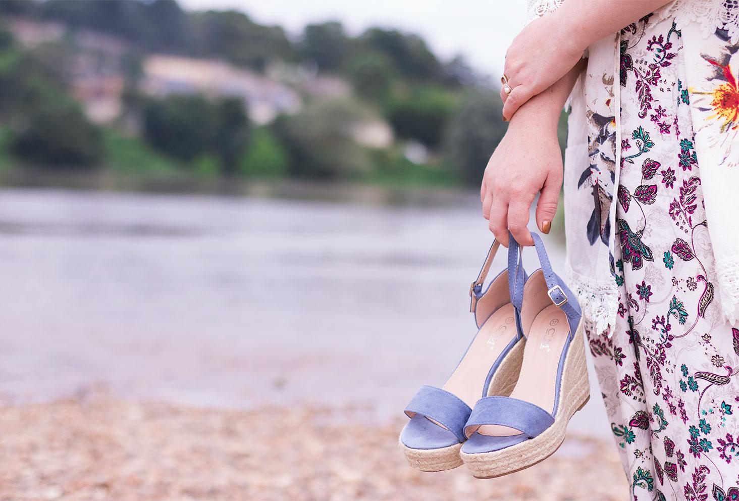 Chaussures compensées bleues Cendriyon dans la main avec la Loire en arrière plan