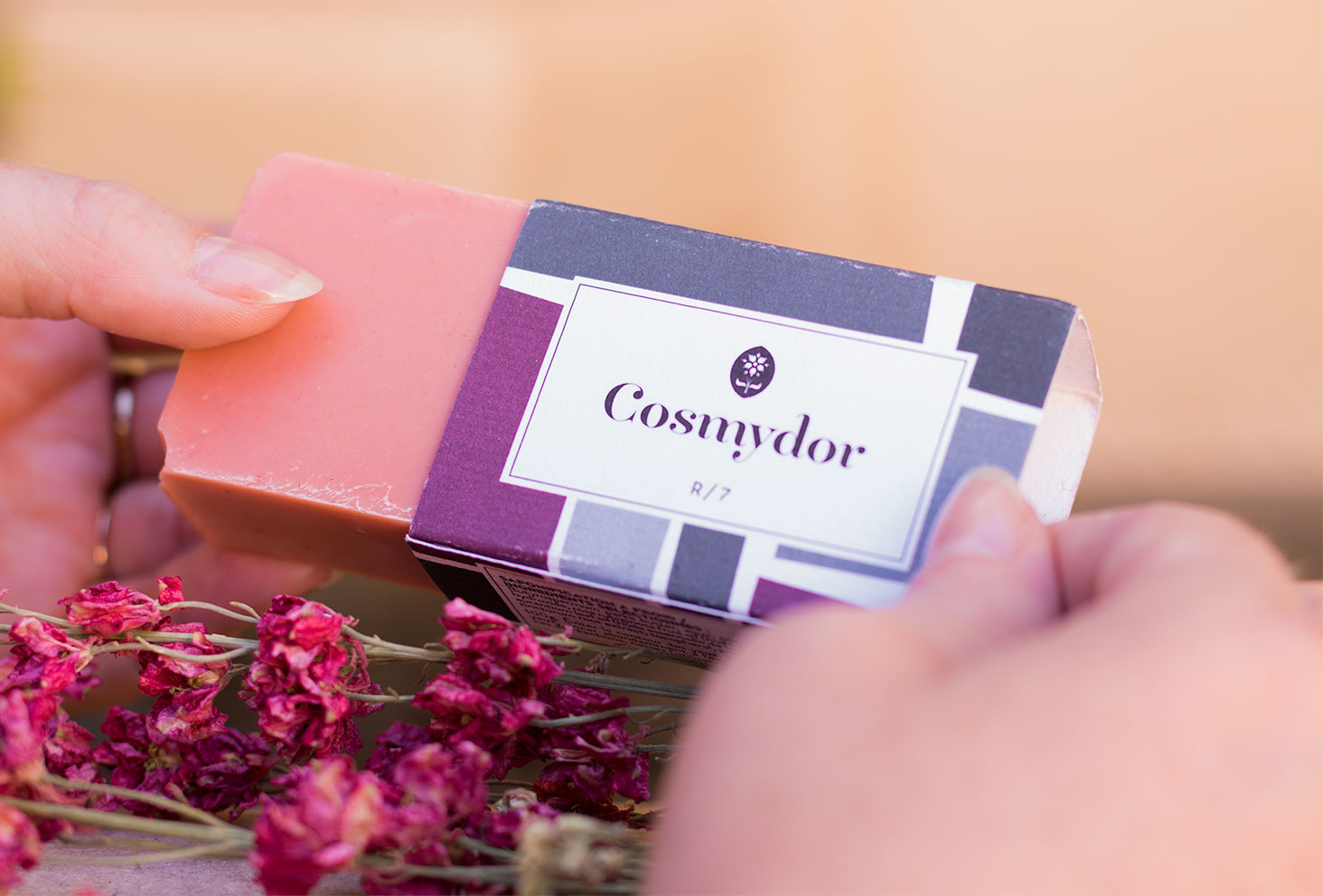 Zoom sur le packaging du savon solide R/7 rose de Cosmydor entre les mains