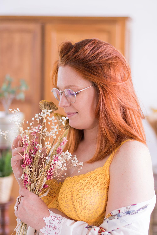 Zoom sur le soutien-gorge jaune en dentelle Pomm'Poire, de profil avec un bouquet de fleurs sèches entre les mains