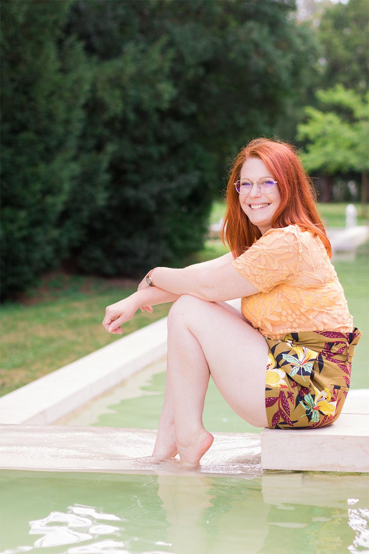 Assise au bord d'une fontaine de profil les pieds dans l'eau, en t-shirt jaune Zara et short taille haute