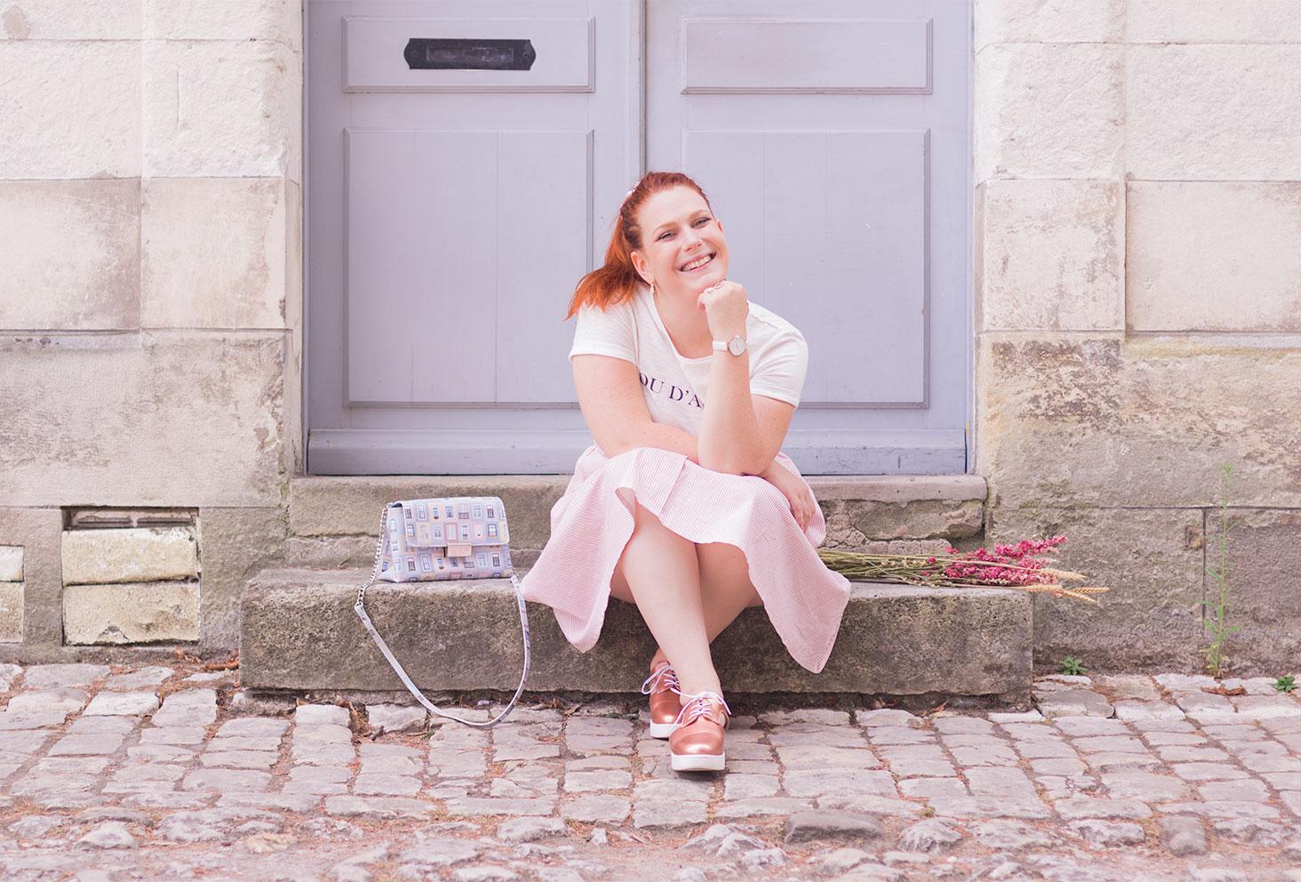Assise sur des marches en pierre en couleurs pastels, la tête posée sur le point