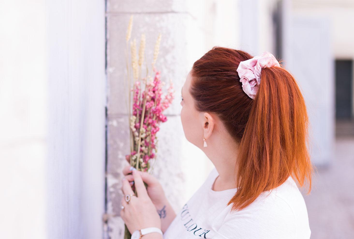 De dos, des fleurs séchées dans les mains, zoom sur une queue de cheval avec un gros chouchou en velours rose Claire's