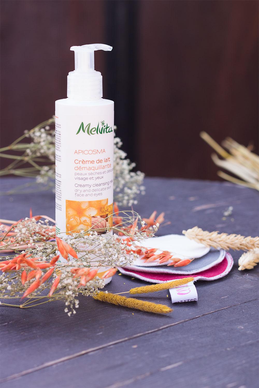 Packaging de la crème de lait démaquillante Melvita sur une table en bois debout au milieu des fleurs séchées