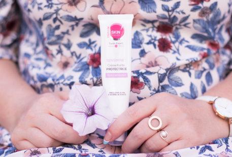 La crème Sensimine de Body Minute, tenue entre les mains sur une robe fleurie bleu et rose