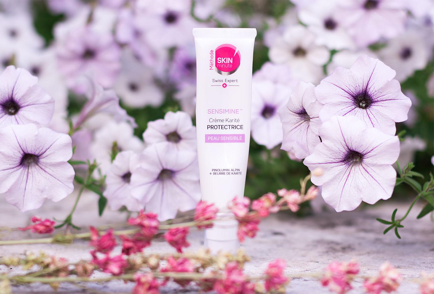 La crème Sensimine protectrice au karité au milieu des fleurs roses pour la routine visage idéale de l'été