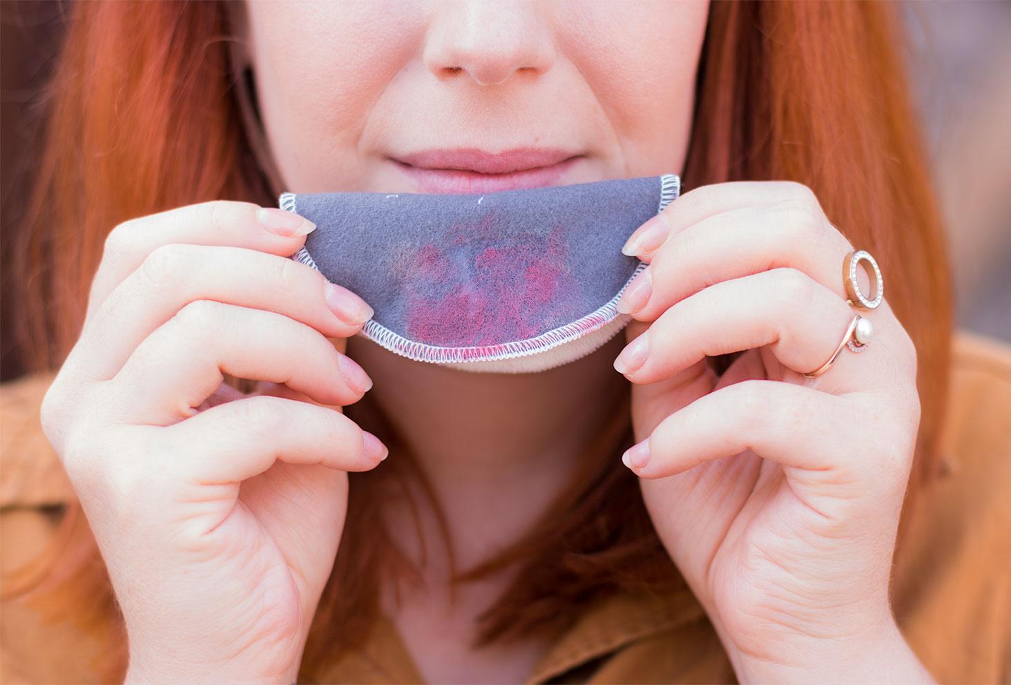 Résidus de rouge à lèvres sur le disque démaquillant lavable de la marque Plim, entre les mains devant la bouche démaquillée