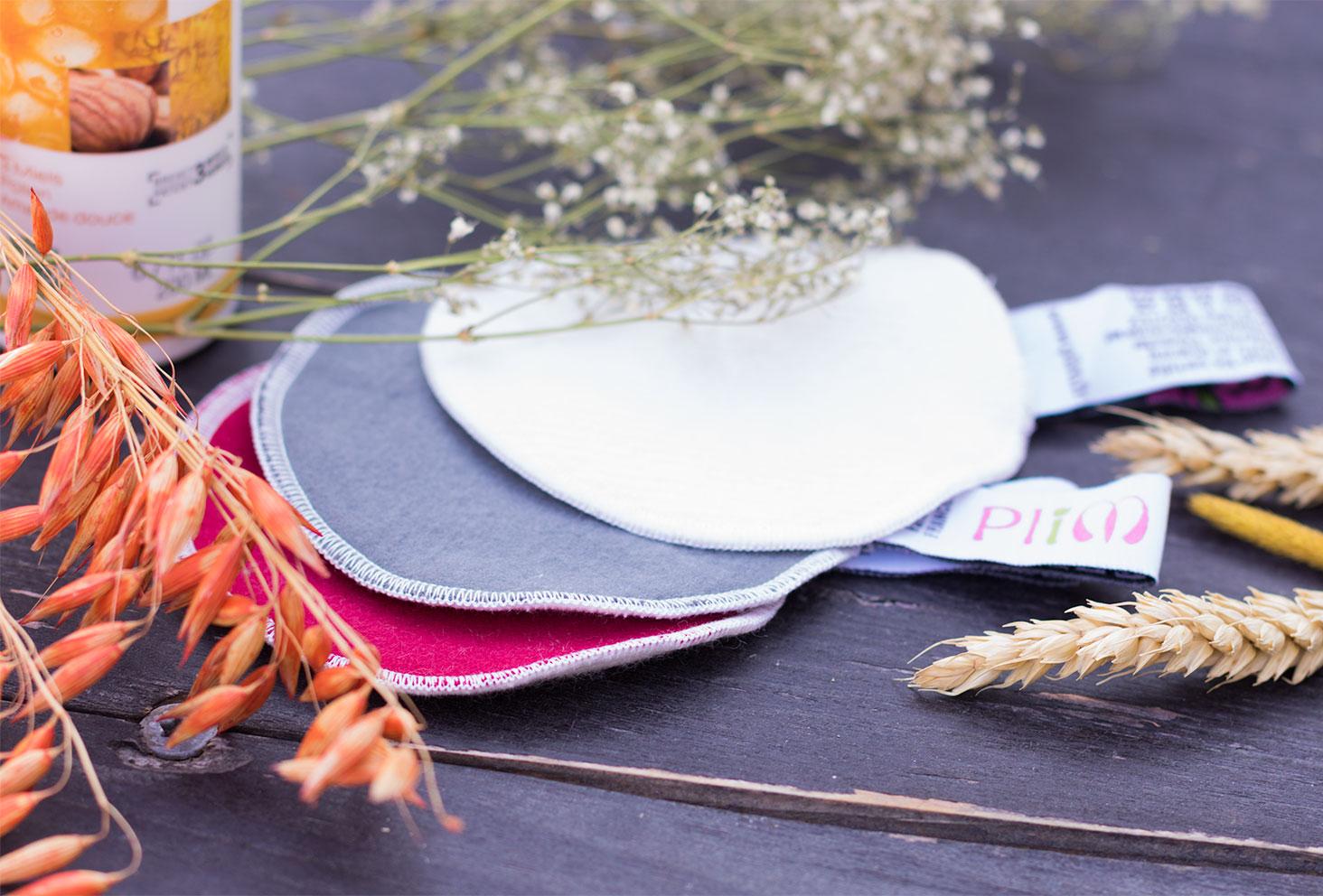 Zoom sur quatre disques démaquillants lavables de la marque PLIM sur une table en bois au milieu des fleurs séchées