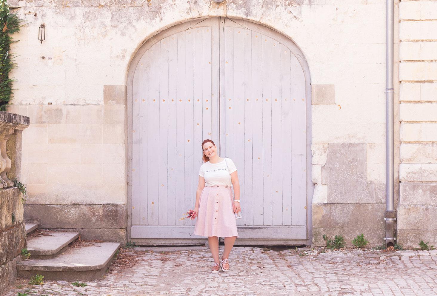 En jupe midi rose, t-shirt à inscriptions et derbies dorées, devant une grande porte en bois grise