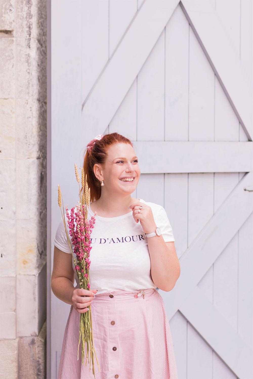 T-shirt blanc Kiabi et jupe midi rose à rayures Kiabi, portés devant une porte en bois grise, avec le sourire et des fleurs séchées dans les mains