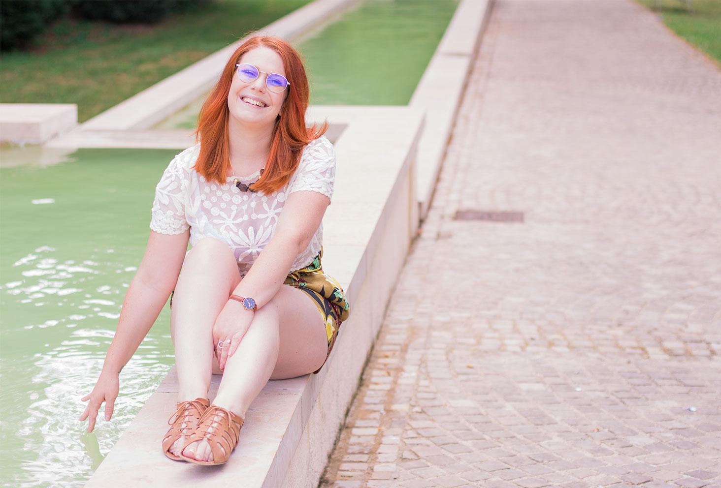 En look Zara tout en dentelle, assise sur le bord d'une fontaine avec la main dans l'eau