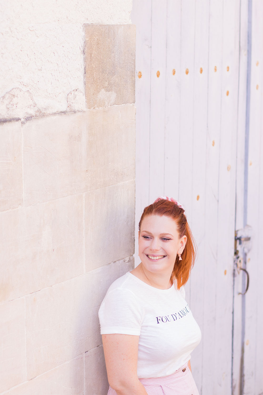"""De profil adossée à un mur en pierre, avec un t-shirt blanc à inscription """"Fou d'amour"""" de Kibi"""