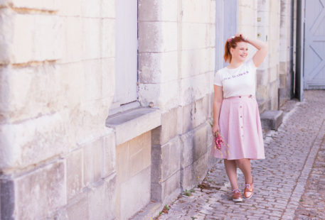 """En train de marcher sur les pavés le long d'un mur en pierre, en jupe midi et t-shirt imprimé """"Fou d'amour"""" Kiabi, des fleurs séchées dans la main"""