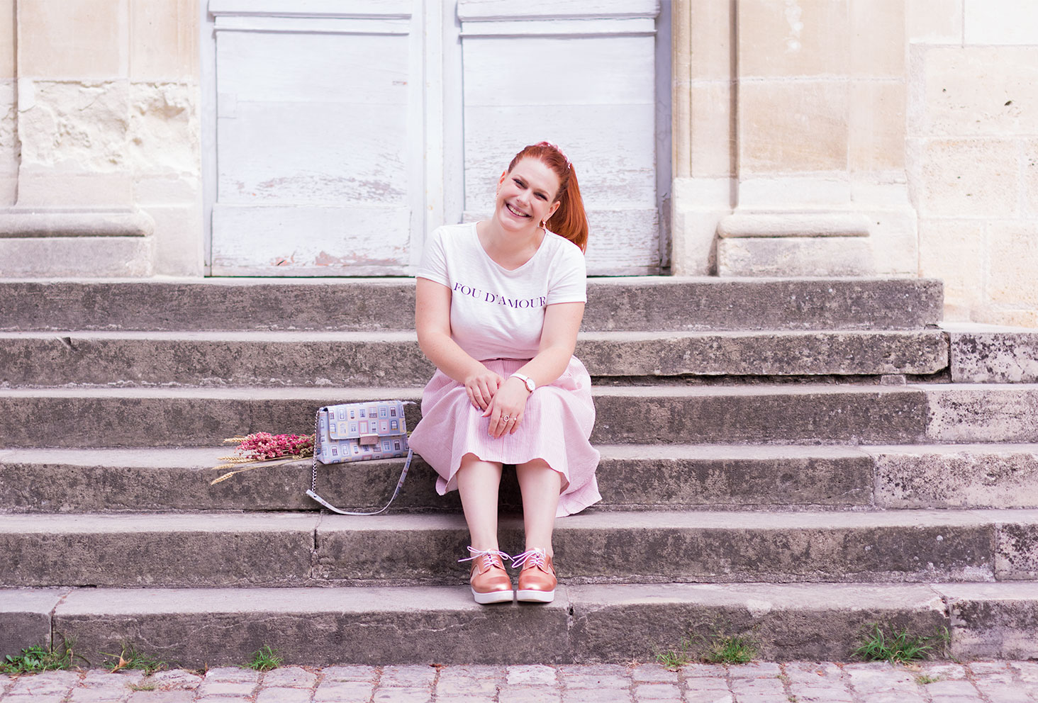 Assise sur des marches en pierre, avec le sourire en look de rentrée tout pastel
