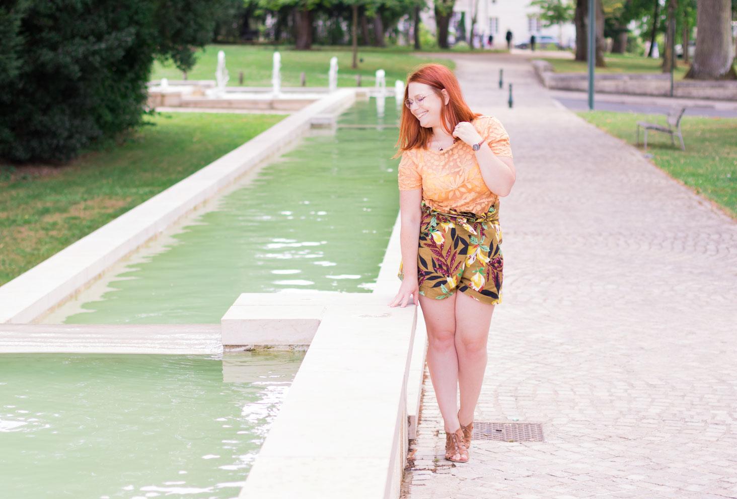 Appuyée sur le bord d'une fontaine en look Zara