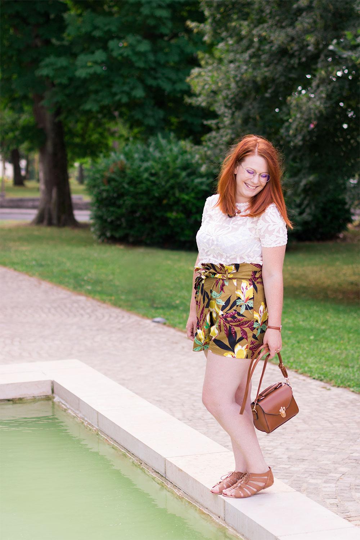 Debout sur le bord d'une fontaine en short taille haute à fleurs Zara et t-shirt en dentelle, pochette marron SheIn dans la main