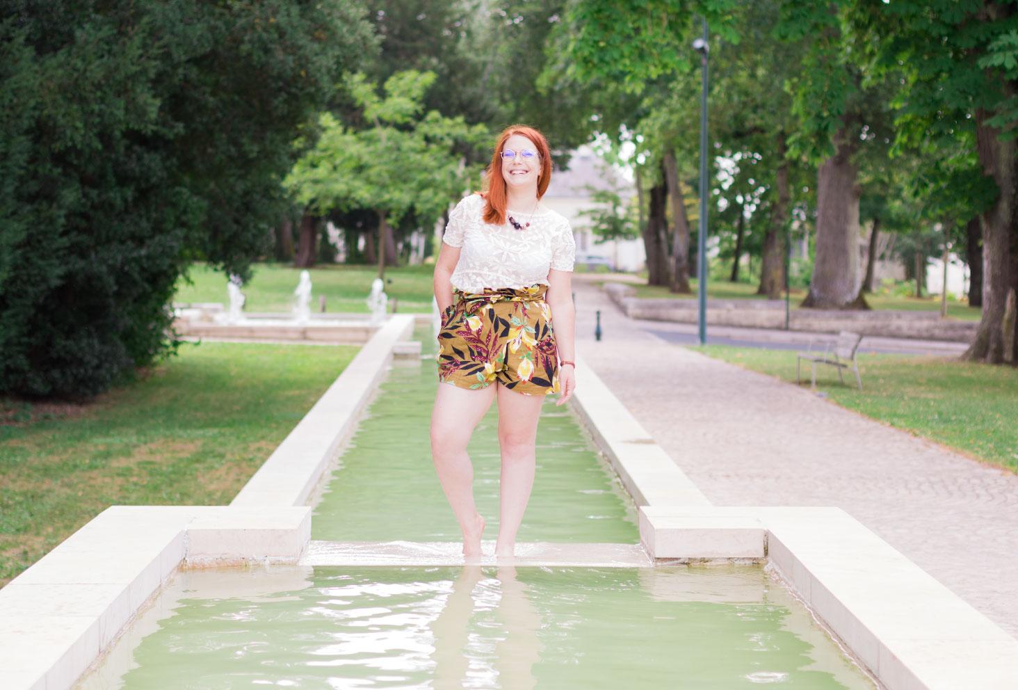 Look entier Zara, t-shirt en dentelle transparent et short kaki à fleurs, les pieds dans l'eau au milieu d'une fontaine
