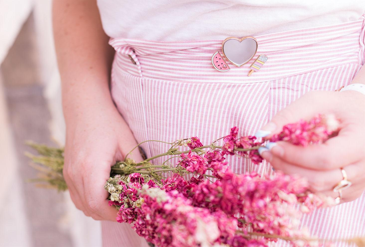 Zoom sur un pin's coeur, pastèque et glace accrochés en haut de la jupe midi rose Shein, des fleurs séchées roses dans les mains