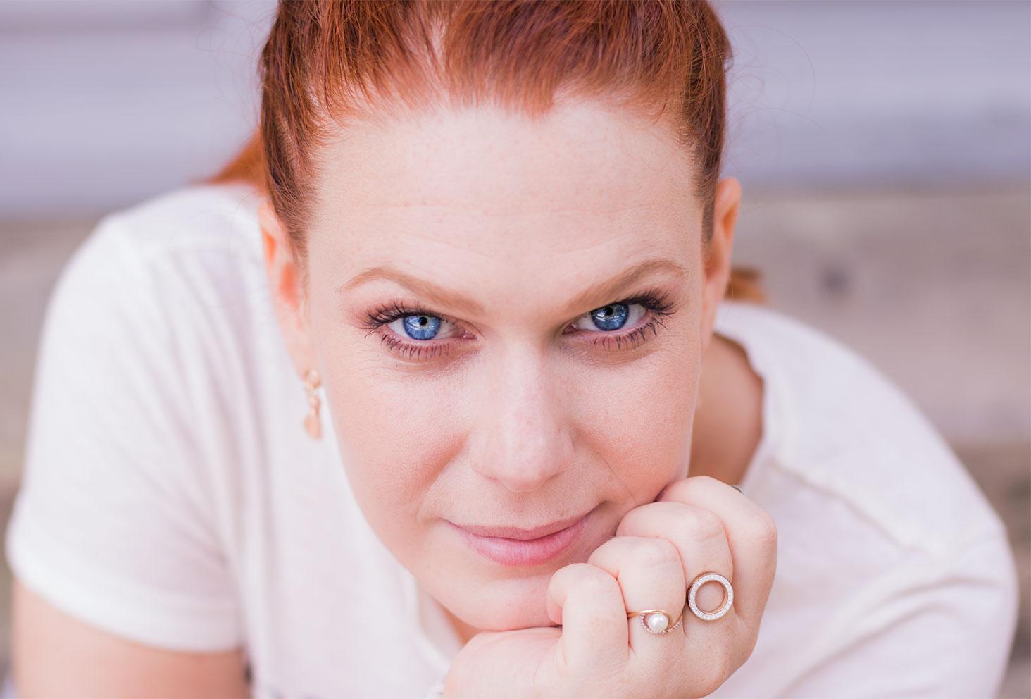 Portrait visage, yeux bleus et cheveux attachés, le menton appuyé sur la main