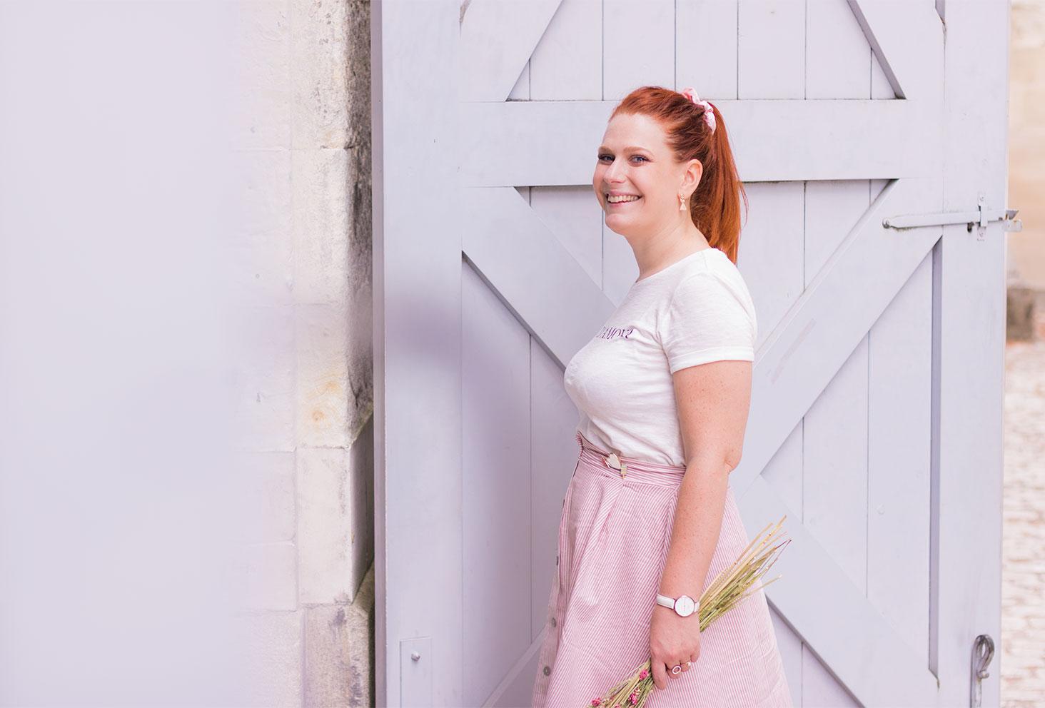 De profil devant une porte de grange en bois grise, avec le sourire et une jupe midi rose Kiabi