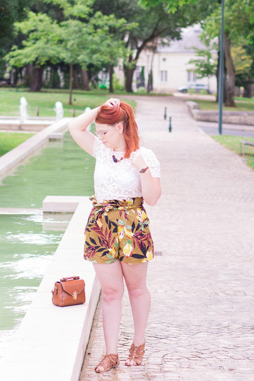 T-shirt blanc en dentelle et short à fleurs sur les bords d'une fontaine