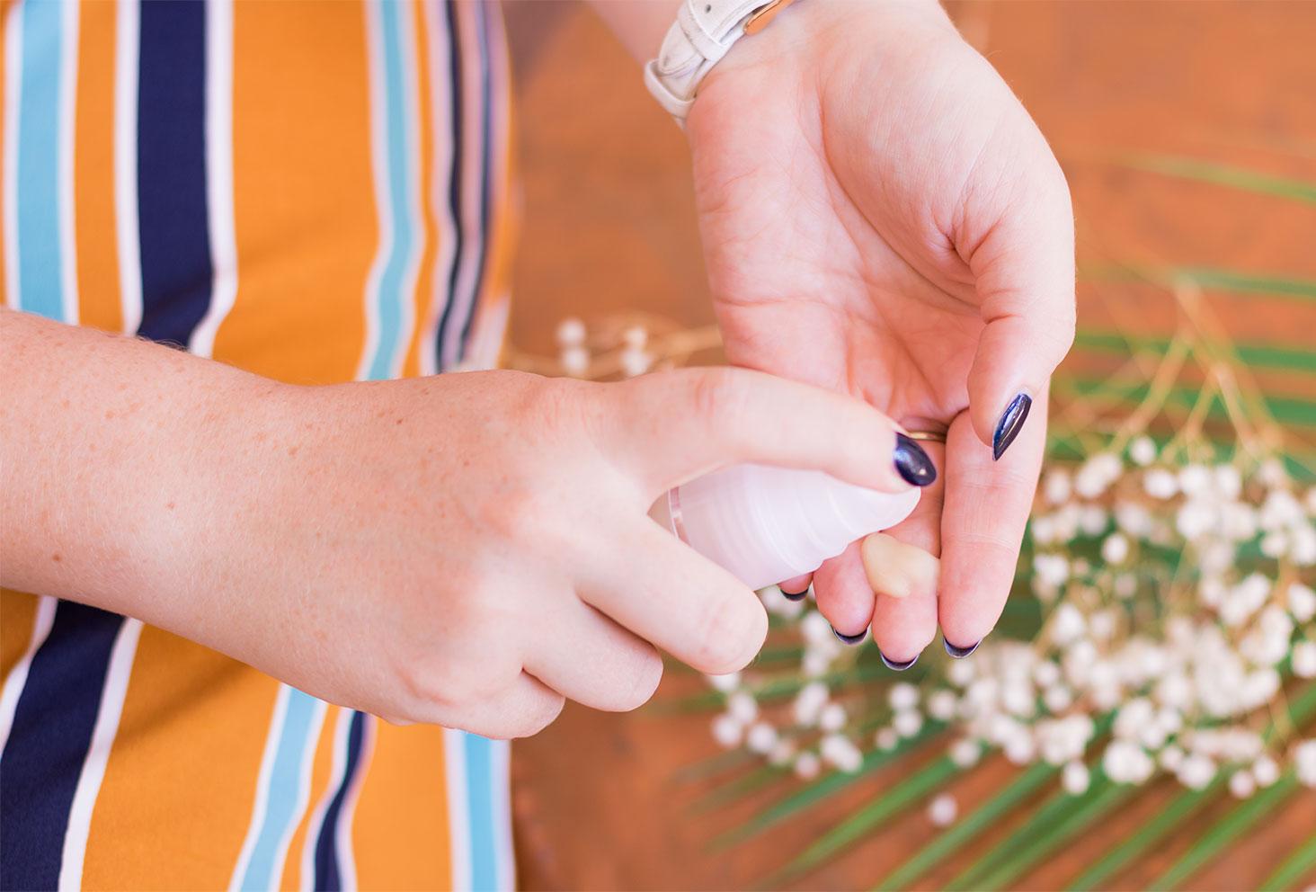La texture du soin contour des yeux de Mlle Agathe en application sur les doigts au dessus des fleurs séchées