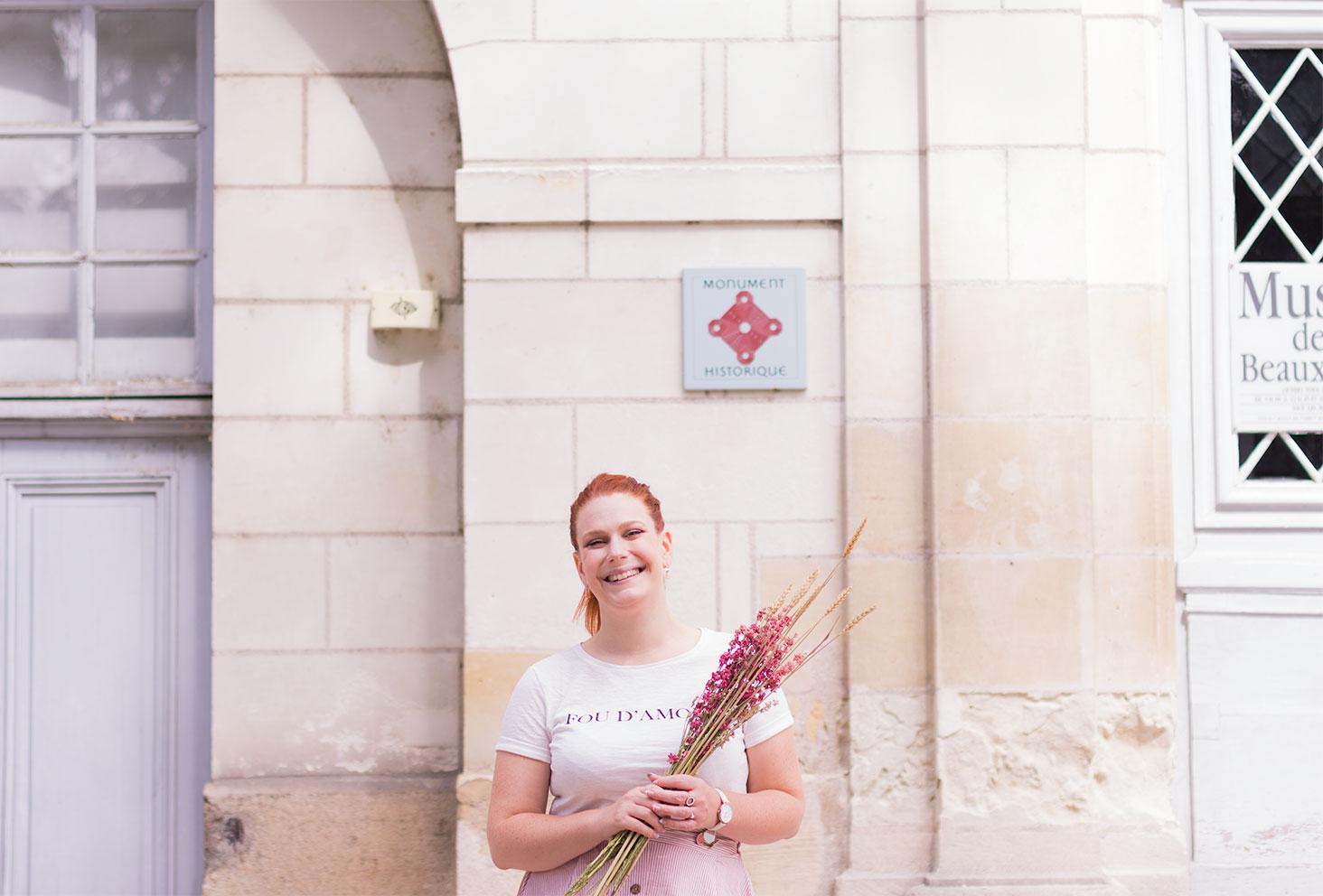 """Devant un mur en pierre, en t-shirt Kiabi blanc """"Fou d'amour"""", des fleurs séchées dans les mains"""