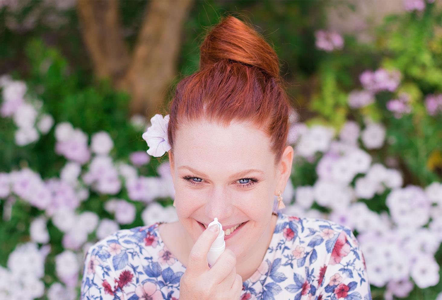 Utilisation de la crème Sensimine au karité de Body Minute sur le bout du nez, avec un chignon sur la tête au milieu des fleurs roses