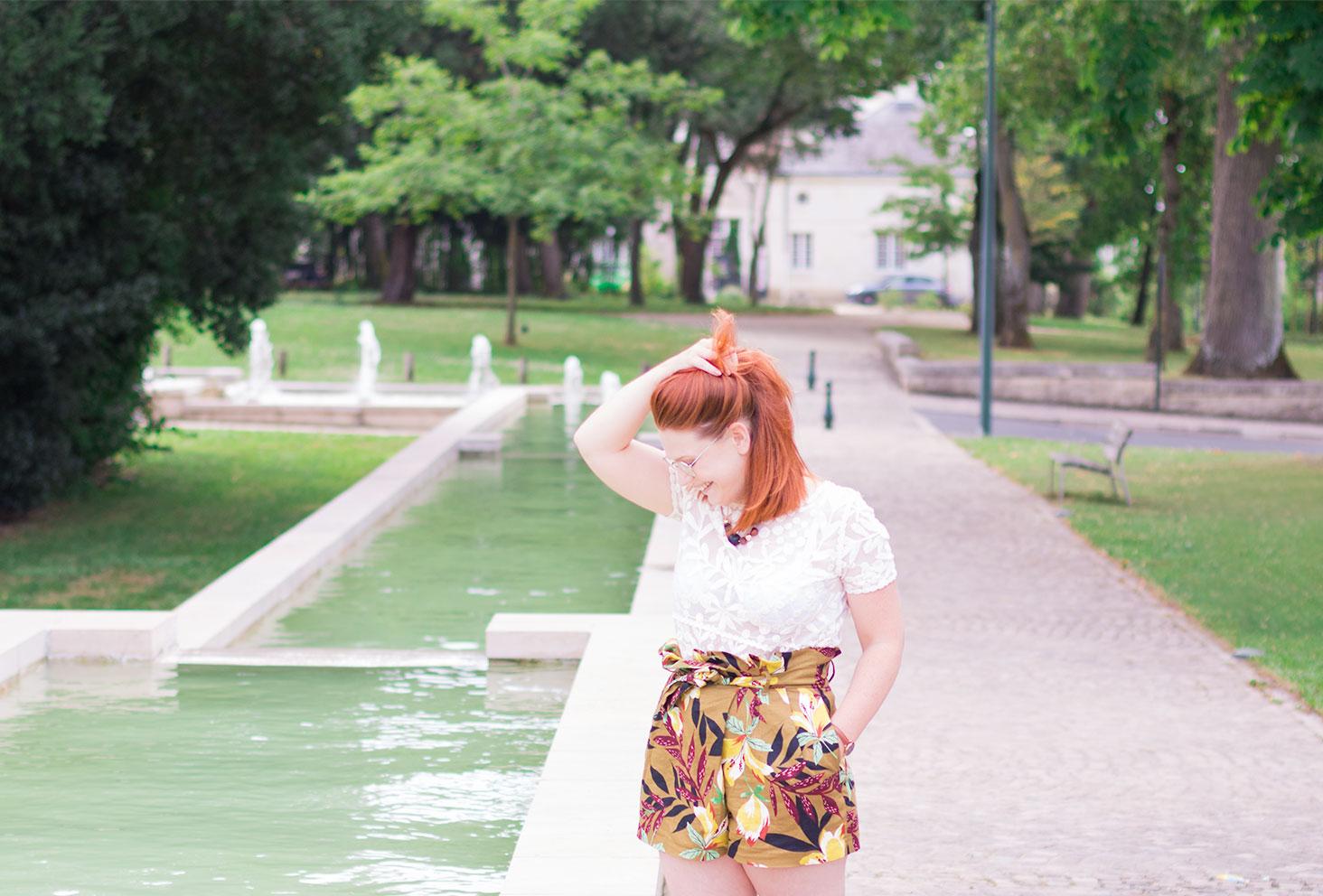 Look short taille haute couleur safari Zara et t-shirt en dentelle blanc debout à côté d'une fontaine