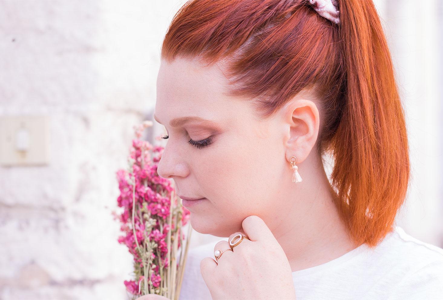 De profil les cheveux roux attachés en queue de cheval haute, des boucles d'oreilles pompons poudrées aux oreilles