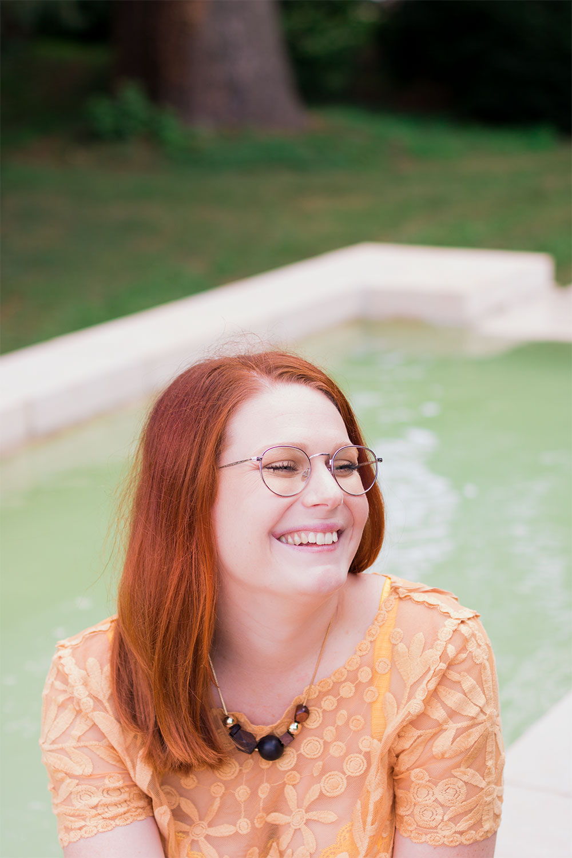 Collier marron en bois MOA porté sur un t-shirt en dentelle jaune Zara, assise sur les bord de la fontaine