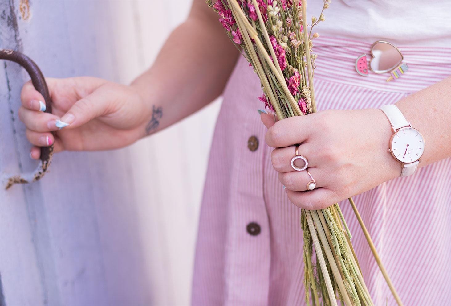 Zoom sur le montre blanche Classic Petite de Daniel Wellington porté avec des fleurs séchées dans la main